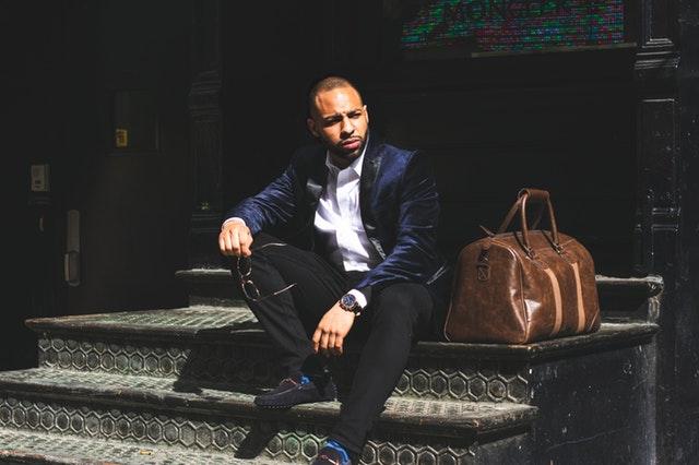 Štýlovo oblečený muž v modrom obleku má vedľa seba položenú koženú tašku.jpg