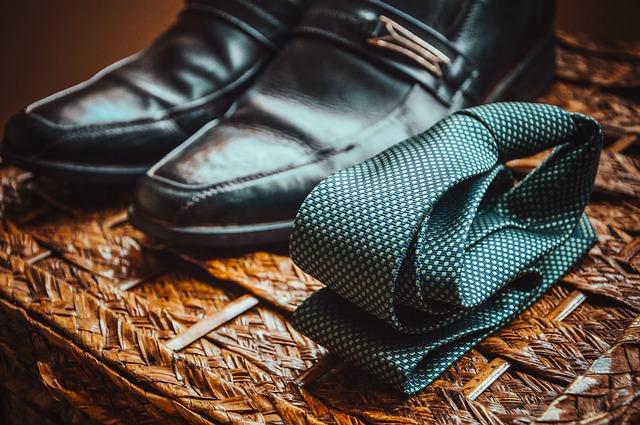 Mužské topánky a kravata položené na hnedom podklade.jpg