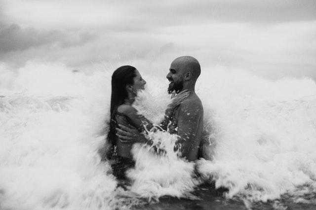 Nahý muž a žena v objatí pri prílive v oceáne