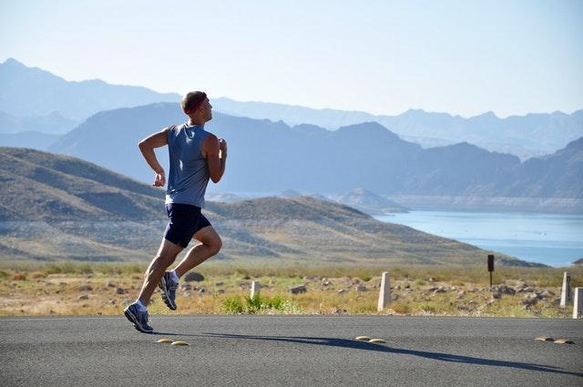 Muž v športovom oblečení beží po asfaltovej ceste.jpg