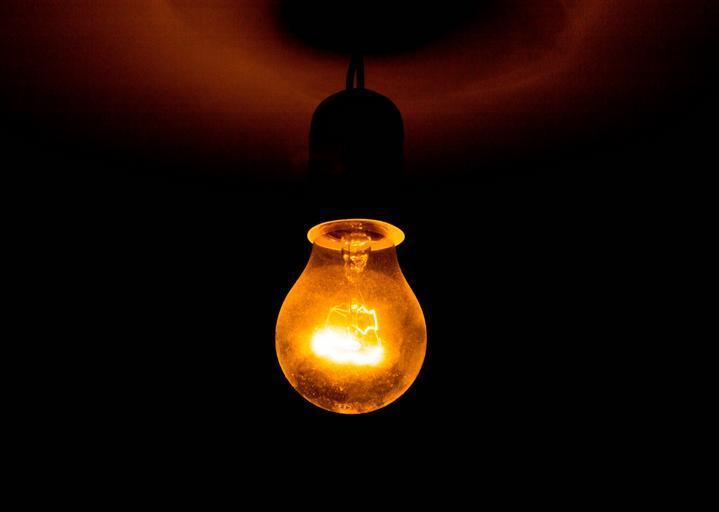 Rozžeravená žiarovka dožlta, čierne pozadie