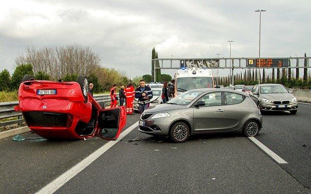 Havária na ceste, červené auto na streche a ľudia naokolo.jpg