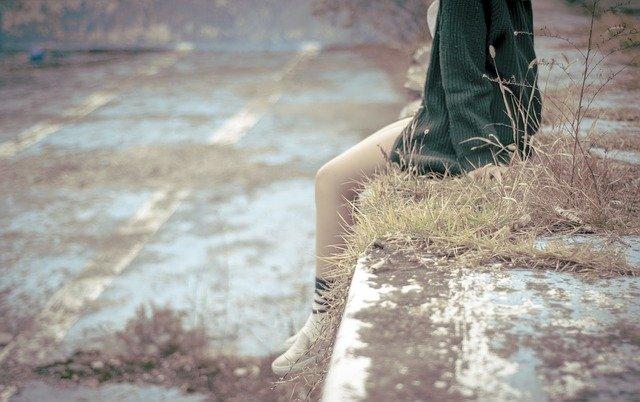 Žena v zelenom svetri sedí na betónovom múriku so spustenými holými nohami.jpg