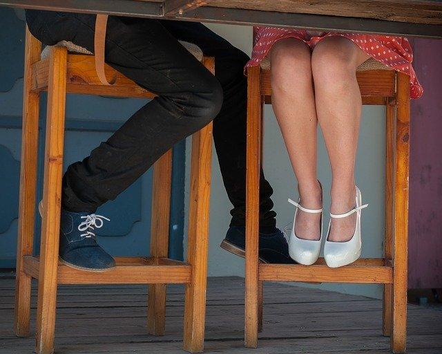 Žena a muž sedia pri drevenom stole a majú nohy pod stolom.jpg